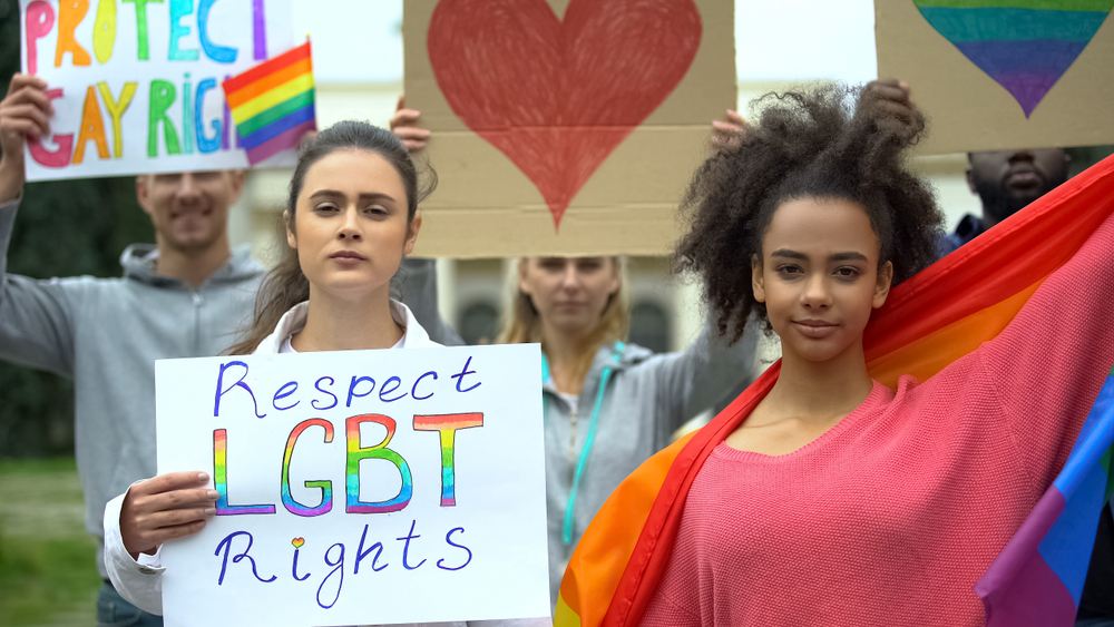 Group of people raising rainbow flags, posters for LGBT rights, gender equality